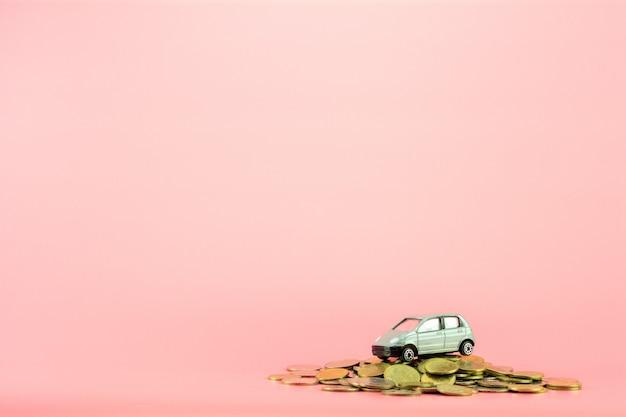 Modèle de voiture miniature grise et pièces d'or s'empilent sur fond rose. Photo Premium