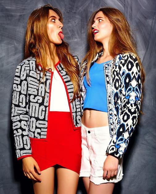 Modèles De Belles Jeunes Femmes Souriantes En Tissu Brillant Hipster D'été Près Du Mur Gris Photo gratuit