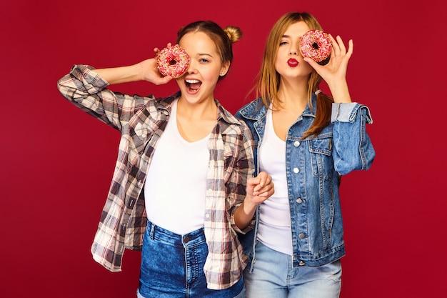 Modèles Féminins Tenant Des Beignets Roses Avec Des Paillettes Photo gratuit