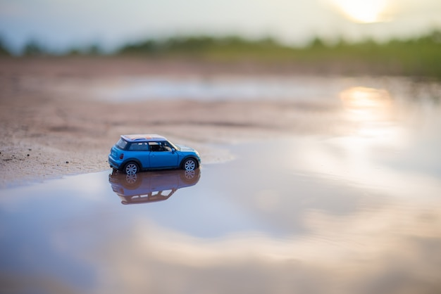Modèles de jouets de voiture sont sur la réflexion de l'eau avec l'arrière-plan flou de la lumière du soleil Photo Premium