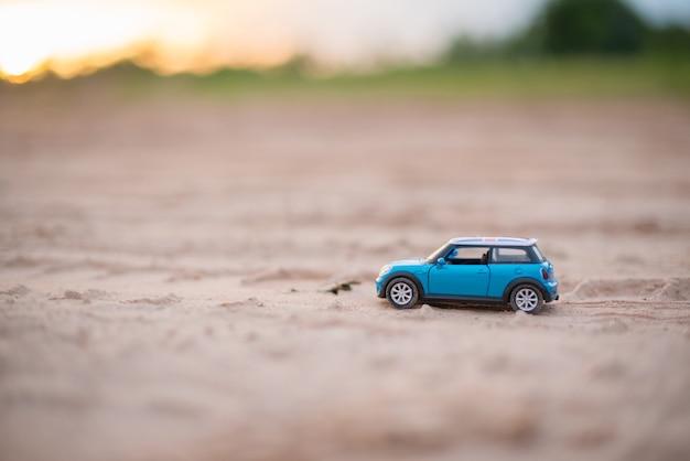 Modèles de jouets de voiture sont sur la route avec l'arrière-plan flou de la lumière du soleil Photo Premium