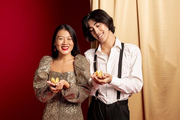 Modèles Souriants Tenant Des Biscuits De Fortune Pour Le Nouvel An Chinois Photo gratuit