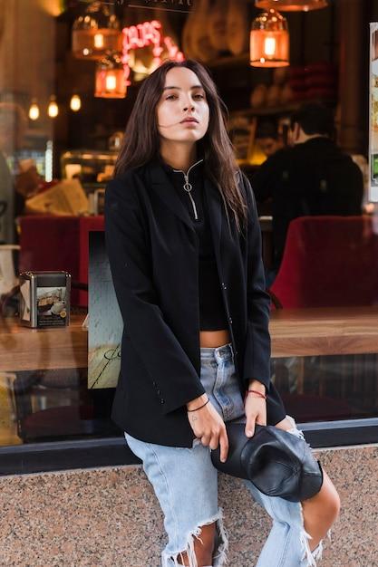Moderne, jeune femme, tenue, casquette, main, séance, devant, fenêtre, restaurant Photo gratuit
