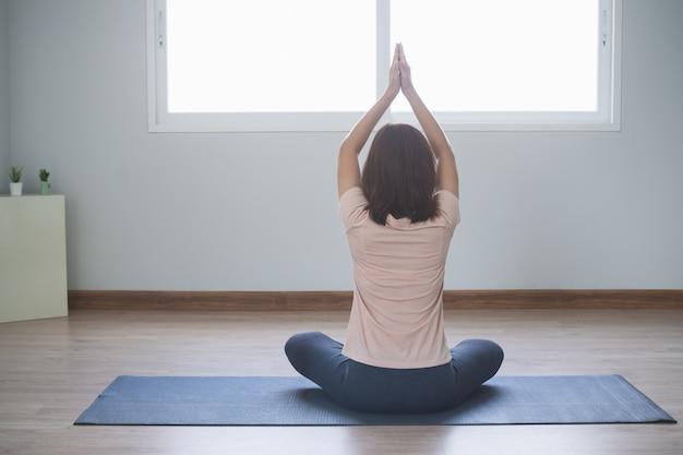 Modes de vie de yoga et de méditation. vue arrière de la belle jeune femme à pratiquer le yoga dans le salon de la maison. Photo Premium