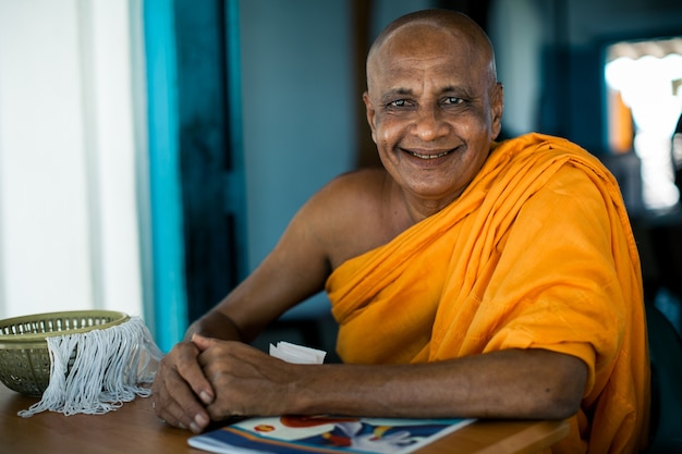 Moine bouddhiste asiatique âgé, souriant à la caméra dans le monastère bouddhiste à la rivière Photo gratuit