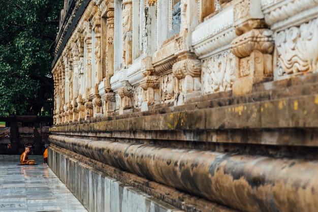 Moine bouddhiste en méditation sous l'arbre bodhi dans la région du temple mahabodhi alors qu'il pleuvait à bodh gaya Photo Premium