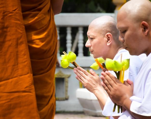 Un moine bouddhiste nouvellement ordonné prie avec un prêtre Photo Premium