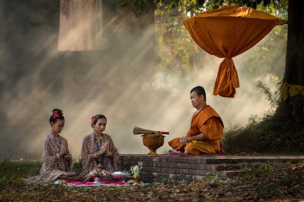 Moines asiatiques, méditation arbre dans l'éclairage du temple. Photo Premium