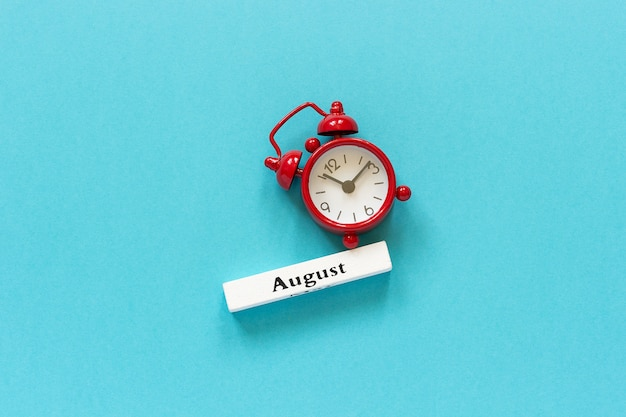 Mois d'été août et réveil rouge sur papier bleu. concept bonjour août Photo Premium
