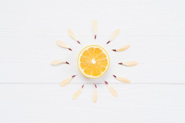 La moitié de citron avec des pétales sur fond blanc Photo gratuit