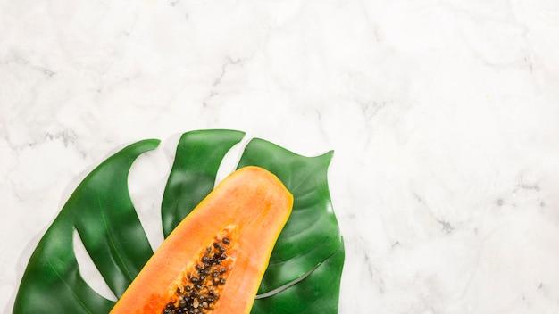 La Moitié Des Fruits De Papaye Sur La Feuille De Monstera Photo gratuit