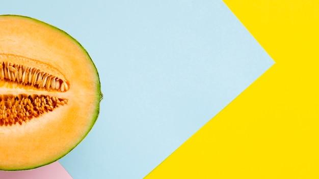 La moitié de melon avec un fond coloré Photo gratuit