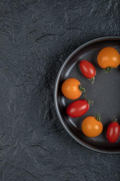 La Moitié Des Tomates Cerises Colorées Dans La Poêle Sur Fond Noir. Photo De Haute Qualité Photo gratuit