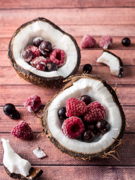 Moitiés de noix de coco avec baies congelées sur un fond en bois foncé Photo Premium
