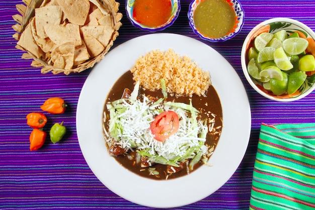 Mole enchiladas nourriture mexicaine avec des sauces au chili Photo Premium