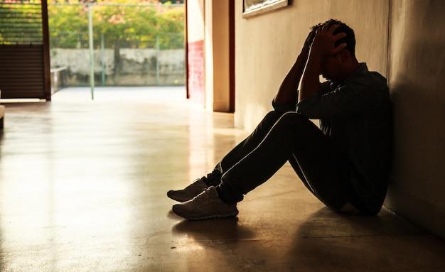 Moment émotionnel: homme assis tenant la tête dans les mains, stressé jeune homme triste ayant mental Photo Premium