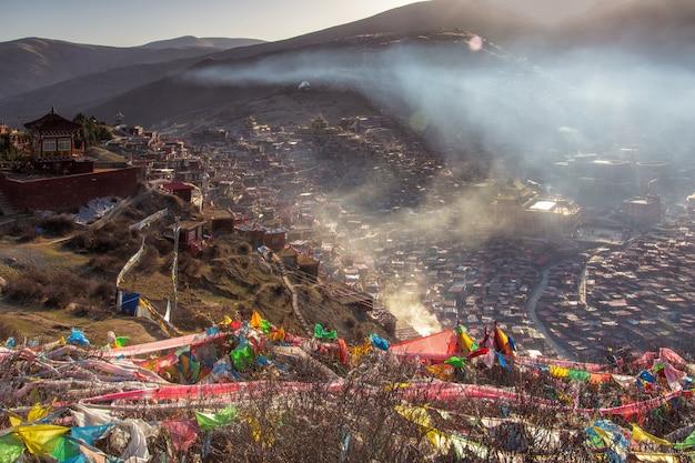 Monastère rouge et domicile à larung gar (académie bouddhiste) au soleil et au ciel bleu Photo Premium