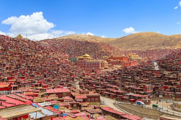 Monastère rouge et domicile à larung gar (académie bouddhiste) au soleil et au fond, ciel bleu Photo Premium