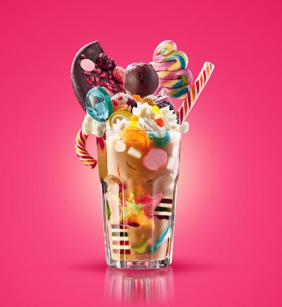 Monster Shake, Freak Caramel Shake Isolé. Cocktail De Milk-shake Coloré Et Festif Avec Des Bonbons, De La Gelée. Gamme De Milkshake Au Caramel Coloré De Différents Bonbons Et Friandises Pour Enfants En Verre. Milkshake Sucré Photo Premium