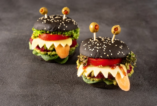 Monstre burger pour la fête d'halloween sur noir Photo Premium
