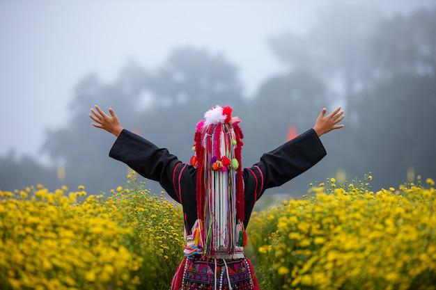 La montagne karen thaïlandaise lève les bras dans le champ des plantes à fleurs de chrysanthèmes Photo Premium