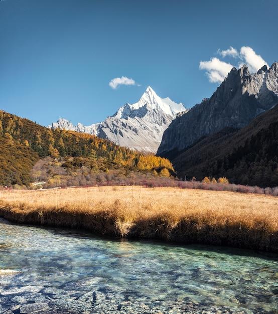 Montagne sacrée de chana dorje avec prairie dorée et rivière de cristal Photo Premium