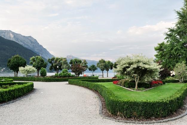 Les montagnes, le lac et la digue de la ville avec des arbres taillés, des arbustes, des pelouses et des parterres de fleurs. Photo Premium