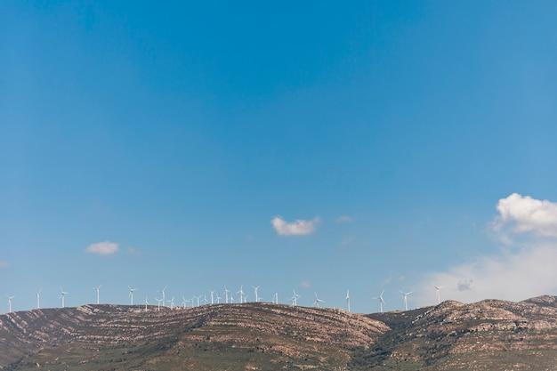 Montagnes avec des moulins à vent sous le ciel bleu Photo gratuit