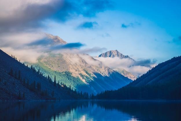 Montagnes de silhouettes bleues étonnantes sous le ciel bleu nuageux. belles ondulations sur l'eau du lac de montagne. nuages bas avant la crête de la montagne. magnifique paysage de montagne. paysage de montagne pittoresque. Photo Premium