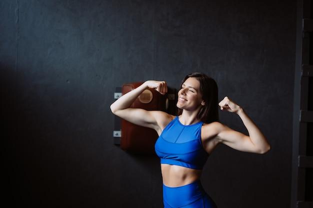 Monter La Femme Posant Sur L'appareil Photo. Entraîneur Personnel Montrant Sa Forme. Beauté Du Sport Moderne. Photo gratuit