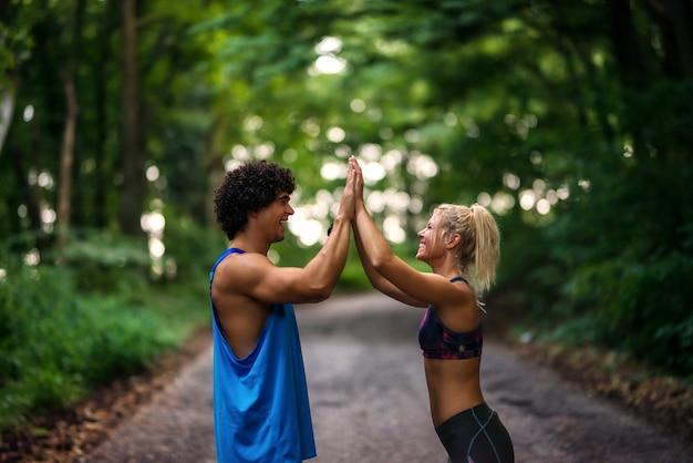 Monter Un Jeune Couple Fort En Se Donnant Un High Five. Debout Sur Une Piste De Course Dans Un Parc. Photo Premium