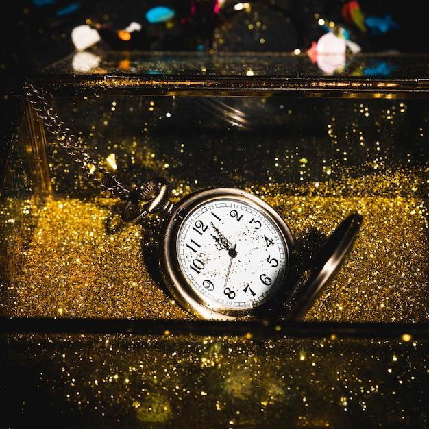 Montre de poche entre paillettes d'or Photo gratuit