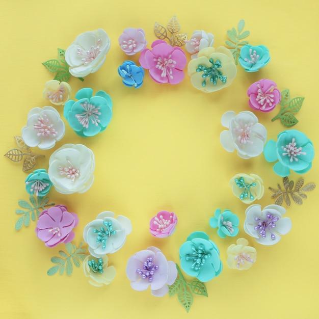 La monture est composée de fleurs artificielles de couleur rose blanche, bleue et jaune sur un fond de papier jaune clair. Photo Premium