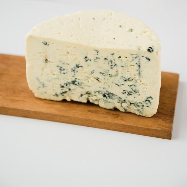 Morceau de fromage bleu sur une planche en bois sur fond blanc Photo gratuit