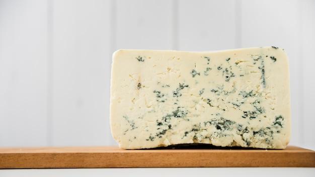 Morceau De Fromage Bleu Sur Une Planche à Découper En Bois Sur Un Bureau Blanc Photo gratuit