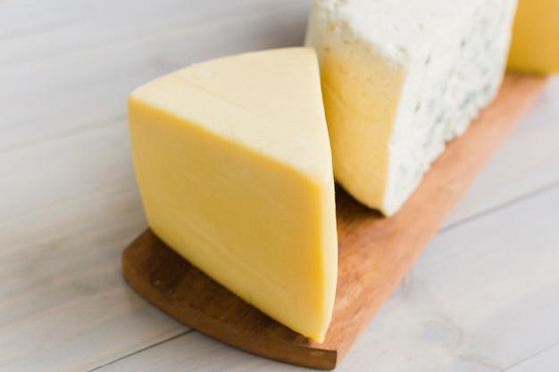Un morceau de fromage sur une planche à découper sur la table en bois Photo gratuit