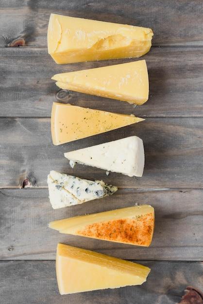 Morceau de fromage triangulaire disposé en rangée sur une planche en bois Photo gratuit