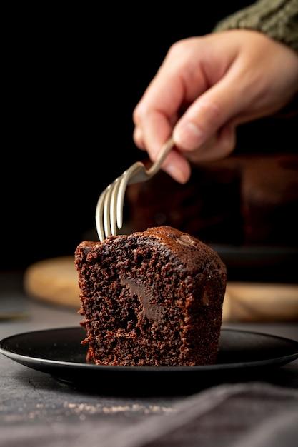Morceau de gâteau au chocolat dans une assiette noire Photo gratuit