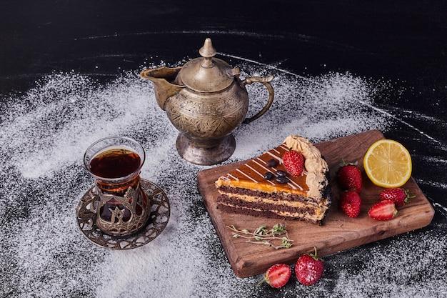 Un Morceau De Gâteau Au Chocolat Décoré De Fruits Sur Fond Sombre Avec Service à Thé Classique. Photo gratuit