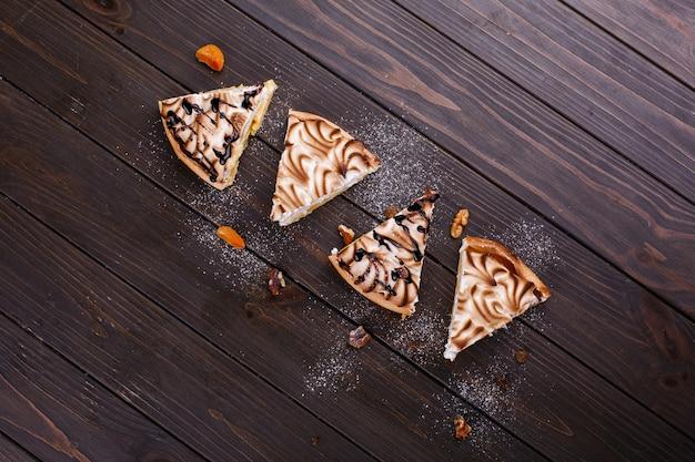 Morceau de gâteau au fromage au citron et crème blanche servi sur une table en bois foncé Photo gratuit