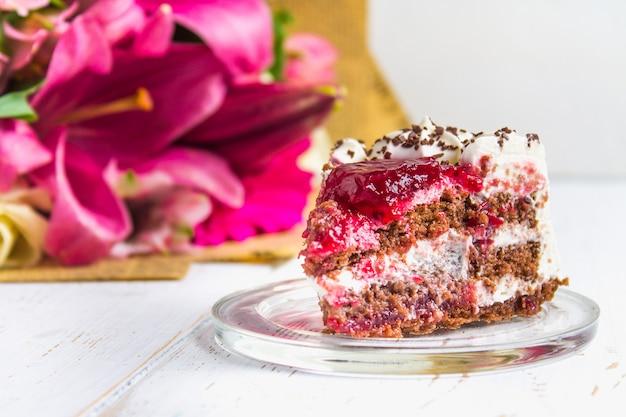 Un morceau de gâteau et un bouquet de fleurs sur une table en bois blanche. Photo Premium