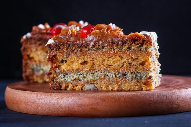 Un morceau de gâteau avec de la crème au caramel et des graines de pavot sur une planche de cuisine en bois, fond noir. Photo Premium