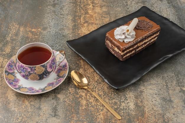 Un Morceau De Gâteau Avec Du Thé Chaud Et Une Cuillère Sur Une Assiette Sombre Photo gratuit