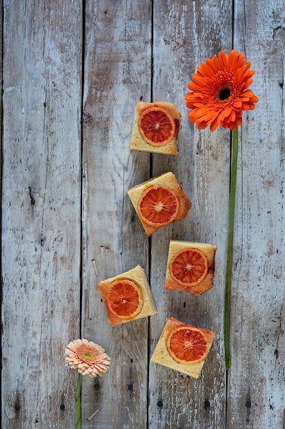 Un morceau de gâteau à l'orange sanguine et une fleur rouge sur fond en bois Photo Premium