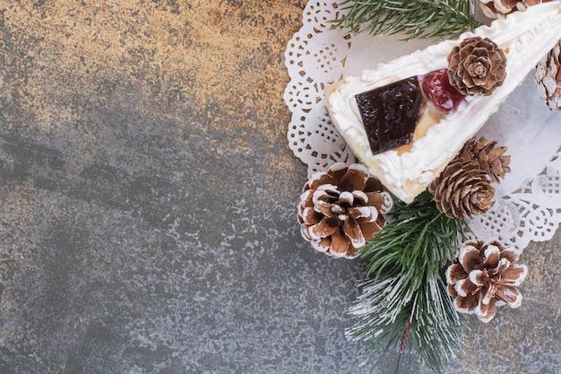 Un Morceau De Gâteau Avec Des Pommes De Pin Sur Une Surface En Marbre Photo gratuit