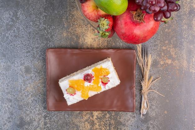 Un Morceau De Gâteau Savoureux Avec Divers Fruits Sur Un Espace En Marbre. Photo gratuit