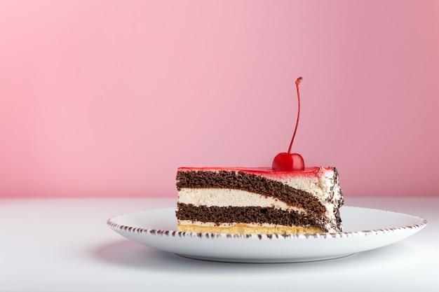 Morceau De Gâteau Vanille Au Chocolat Et Cerise Au Marasquin. Gâteau De Vue De Côté Sur Fond Rose. Photo Premium