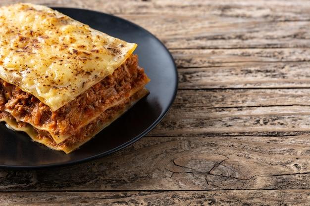 Morceau De Lasagne à La Viande Sur Plaque Noire Sur Table En Bois Rustique Photo Premium
