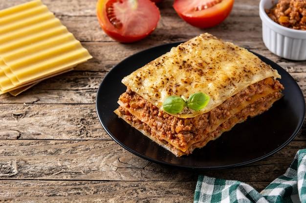 Morceau De Lasagne à La Viande Sur Plaque Noire Sur Table En Bois Photo Premium