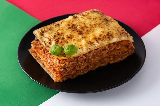 Morceau De Lasagne à La Viande Sur Une Plaque Noire Photo Premium